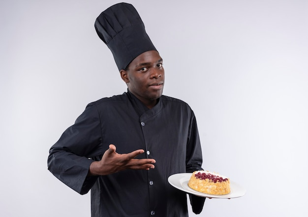 Młody zdezorientowany kucharz afroamerykański w mundurze szefa kuchni trzyma i wskazuje ciasto na talerzu na białym tle z miejsca na kopię