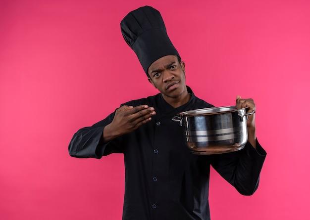 Młody zdezorientowany kucharz afroamerykański w mundurze szefa kuchni trzyma rondel i wskazuje ręką na różowej ścianie