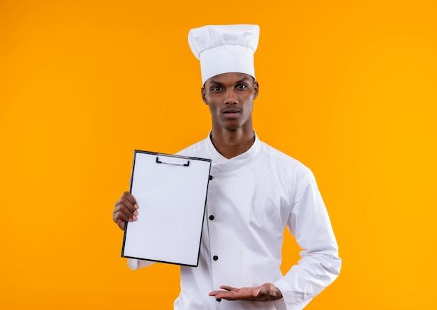 Młody zdezorientowany kucharz afroamerykański w mundurze szefa kuchni trzyma schowek i trzyma rękę otwartą na białym tle na pomarańczowej ścianie