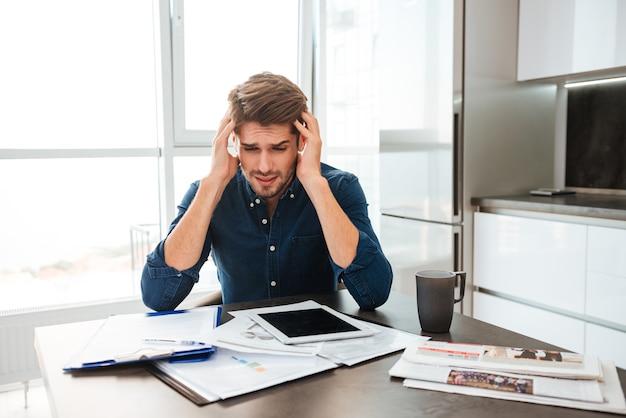 Młody zdezorientowany mężczyzna analizuje finanse, trzymając głowę rękami. siedząc przy stole z tabletem i dokumentami