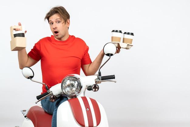 Młody zdezorientowany mężczyzna kurier w czerwonym mundurze siedzi na skuterze trzymając zamówienia na żółtej ścianie