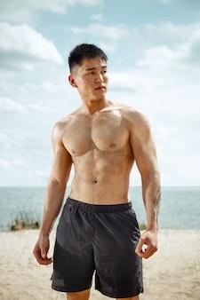 Młody zdrowy mężczyzna sportowiec ćwiczeń na plaży. signle męski model shirtless szkolenia powietrza nad brzegiem rzeki w słoneczny dzień. pojęcie zdrowego stylu życia, sportu, fitness, kulturystyki.