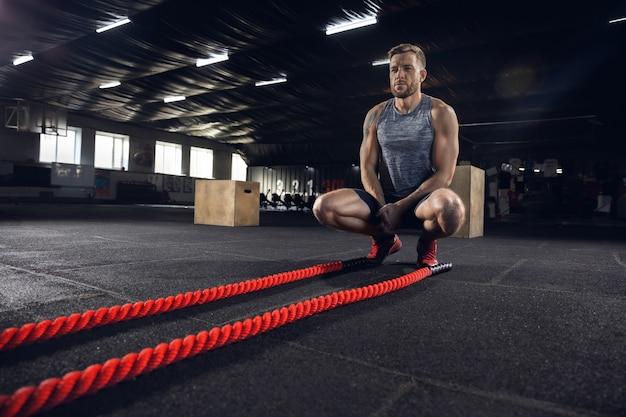 Młody zdrowy mężczyzna sportowiec ćwiczeń na siłowni