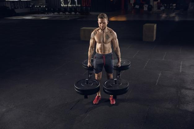 Młody zdrowy mężczyzna, sportowiec ćwiczeń, pozowanie ze sztangą w siłowni