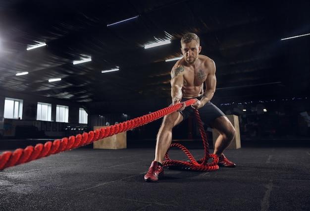 Młody zdrowy mężczyzna, sportowiec robi ćwiczenia z linami w siłowni. samotny model ciężko trenujący i trenujący górną część ciała. pojęcie zdrowego stylu życia, sportu, fitnessu, kulturystyki, dobrego samopoczucia.