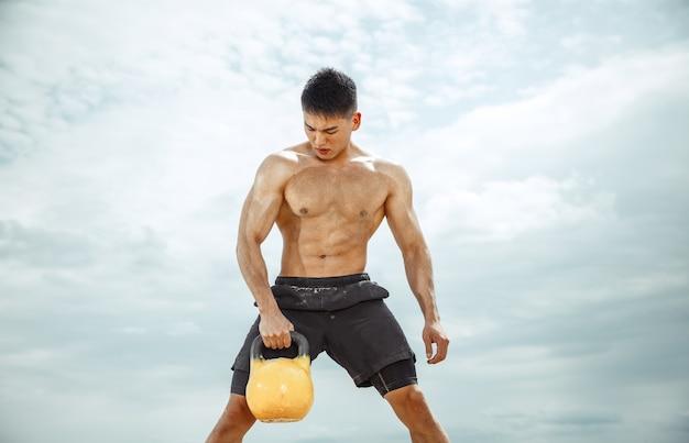 Młody zdrowy mężczyzna sportowiec robi ćwiczenia z wagą na plaży