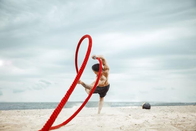 Młody zdrowy mężczyzna sportowiec robi przysiady na plaży