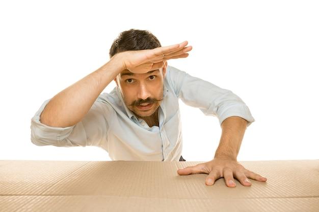 Młody zdumiony mężczyzna otwierający największą paczkę pocztową na białej ścianie