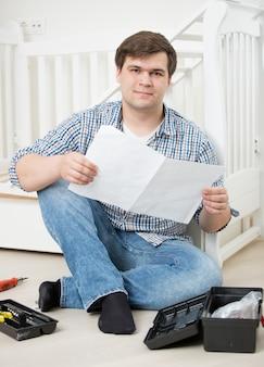 Młody zdziwiony mężczyzna czyta instrukcje montażu do łóżeczka dziecka