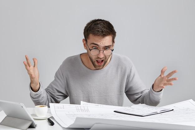 Młody zdziwiony młody architekt czuje się oburzony, patrzy na rysunki na stole, zdaje sobie sprawę, że popełnił błąd