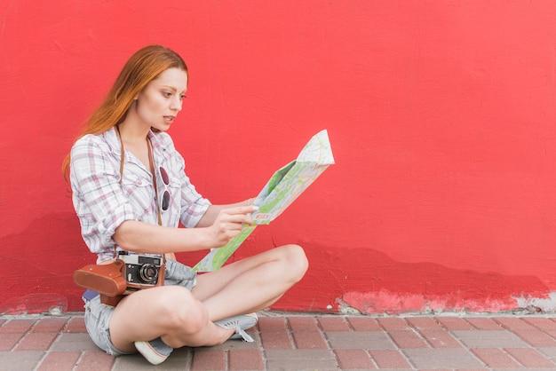 Młody żeński badający mapy obsiadanie na ziemi