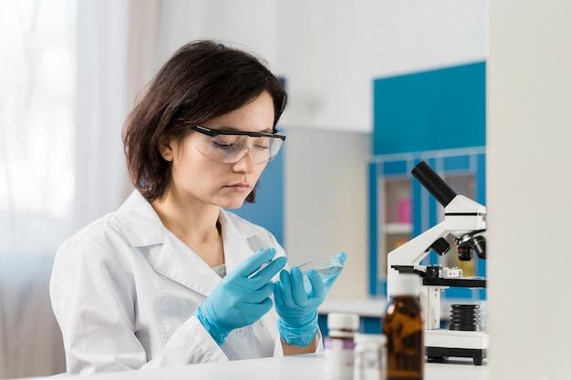 Młody żeński chemik jest ubranym rękawiczki
