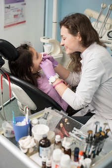 Młody żeński dentysta taktuje cierpliwych dziewczyna zęby przy stomatologicznym biurem. koncepcja stomatologii, medycyny, stomatologii i opieki zdrowotnej.