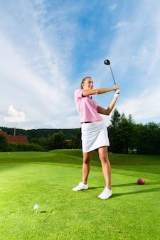 Młody żeński golfowy gracz na kursie robi golfowej huśtawce