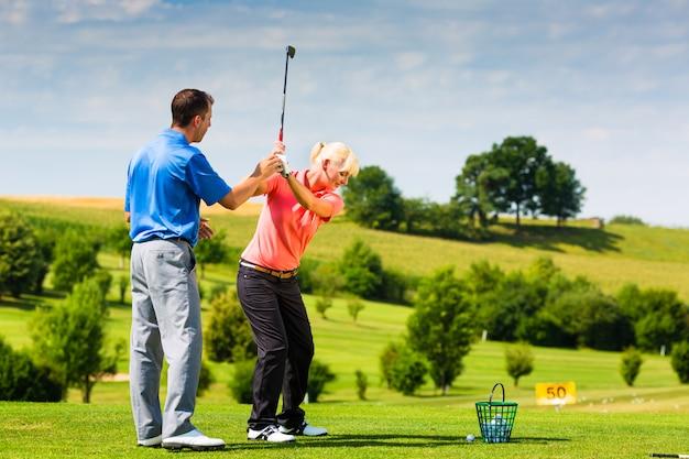 Młody żeński golfowy gracz na kursie