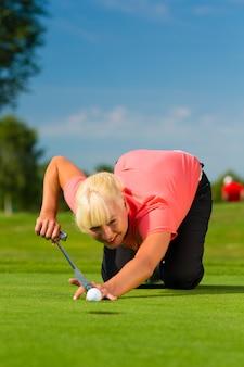 Młody żeński gracz w golfa na kursie stawia na