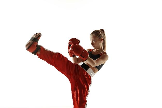 Młody żeński kickboxing myśliwiec szkolenia na białym tle na białej ścianie. kaukaski blondynka w czerwonej odzieży sportowej praktykujących w sztukach walki. pojęcie sportu, zdrowego stylu życia, ruchu, akcji, młodości.