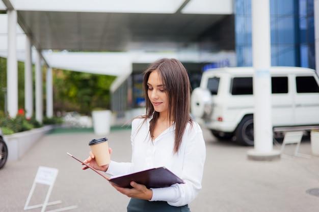 Młody żeński kierownik jest ubranym spódnicę i bluzkę trzyma falcówkę z dokumentami i filiżanką kawy