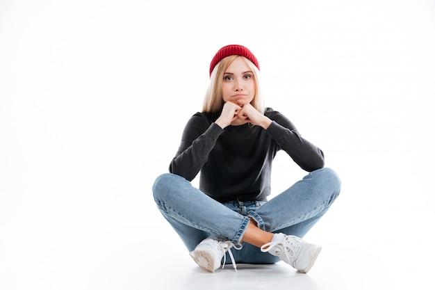 Młody żeński modniś siedzi na podłoga