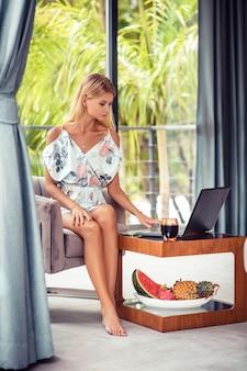 Młody żeński obsiadanie na sa używać laptop w pokoju hotelowego wakacje. talerz z owocami tropikalnymi blisko niej