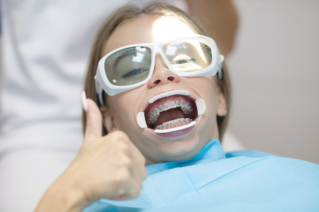 Młody żeński pacjent siedzi w stomatologicznym krześle z nawiasami klamrowymi na zębach, uśmiecha się aprobaty i pokazuje po leczeniu przy nowożytną stomatologiczną kliniką