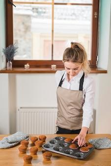 Młody żeński piekarz usuwa muffins od babeczki foremki tacy