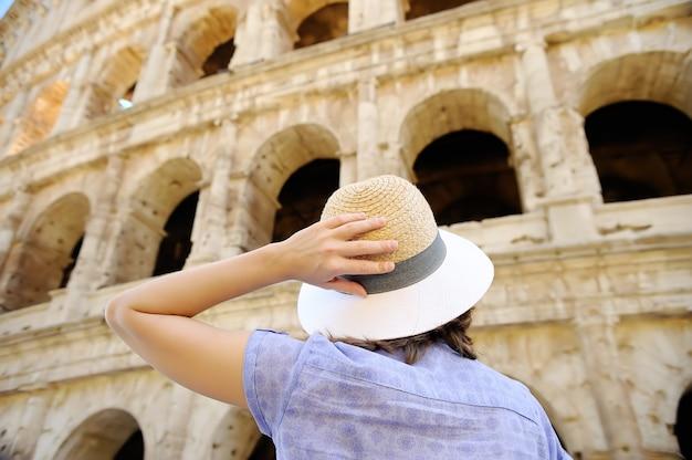 Młody żeński podróżnik patrzeje na sławnym colosseum w rzym.