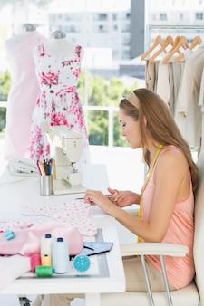 Młody żeński projektant mody pracuje na tkaninach