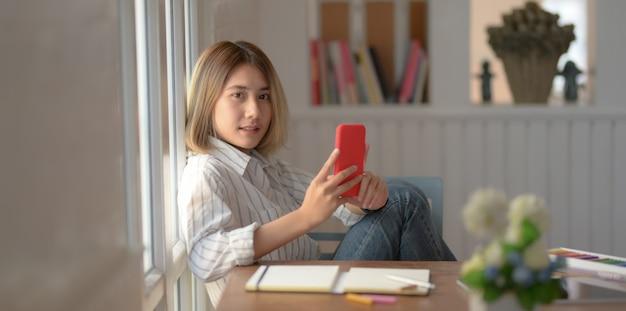 Młody żeński projektanta mienia smartphone i ono uśmiecha się podczas gdy siedzący na krześle