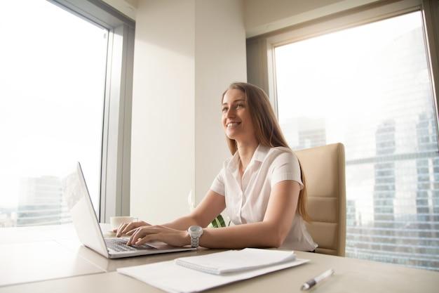 Młody żeński przedsiębiorca czuje szczęśliwy przy miejscem pracy