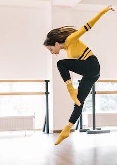 Młody żeński tancerz ćwiczy w tana studiu