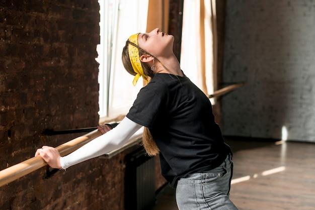Młody żeński tancerz rozciąga jej ręki na barre