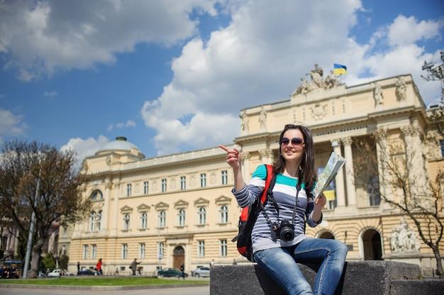 Młody żeński turysta z mapą i kamerą