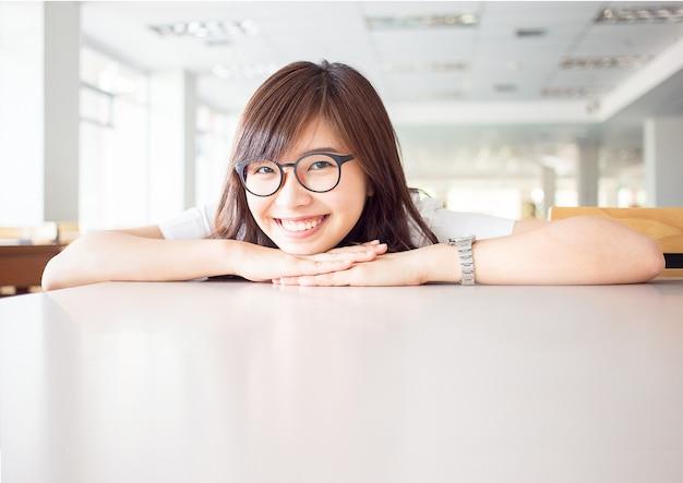 Młody żeński uczeń jest uśmiechnięty z pustą kopii przestrzenią na biurku w bibliotece w kampusie uniwersytet
