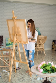 Młody żeński uczeń ma klasy w sztuki studiu, uczy się rysować kwiaty