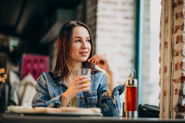 Młody żeński uczeń pracuje na laptopie w barze i je pizzę