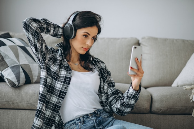 Młody żeński uczeń słucha muzykę przez telefonu na słuchawkach