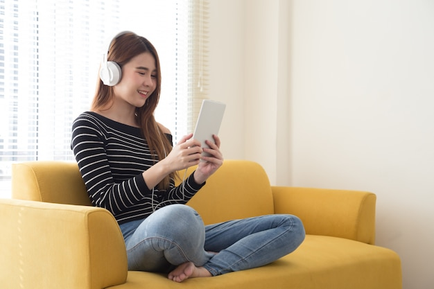 Młody żeński uczeń uczy się online lub czyta ebook