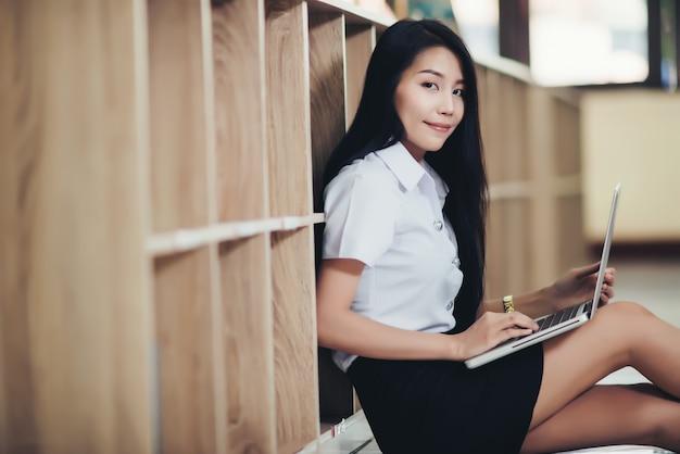 Młody żeński uczeń używa laptop przy biblioteką