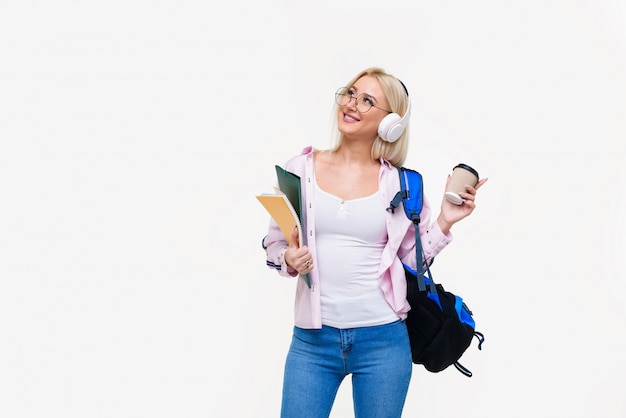 Młody żeński uczeń w hełmofonach z plecakiem pije kawę, ono uśmiecha się. uruchomienie, freelancer. nauka języków obcych online, przygotowanie do egzaminu