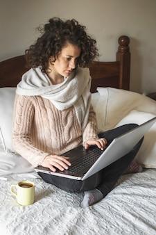 Młody żeński używa laptop na łóżku