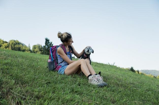 Młody żeński wycieczkowicz bierze przerwy obsiadanie w trawie