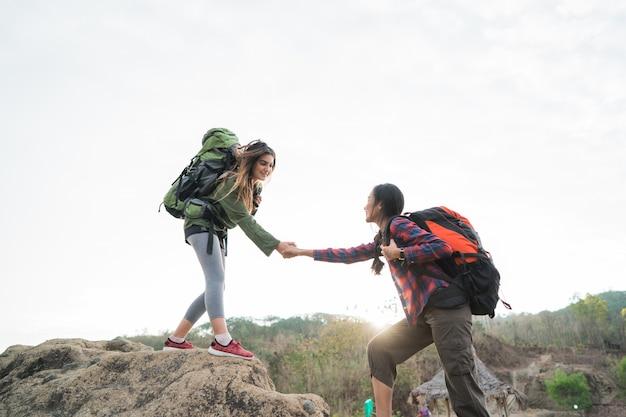 Młody żeński wycieczkowicz pomaga przyjacielowi podczas trekking