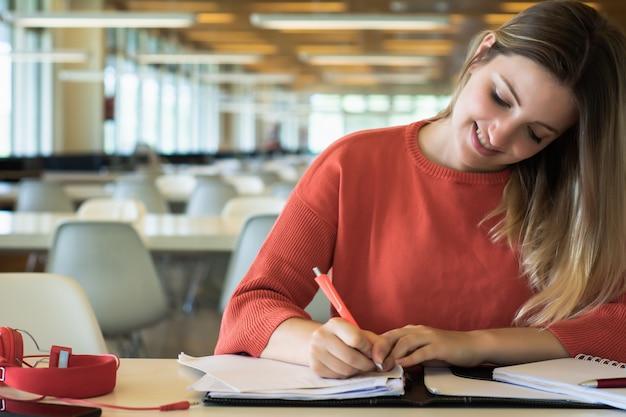 Młody żeńskiego ucznia studiowanie w bibliotece.