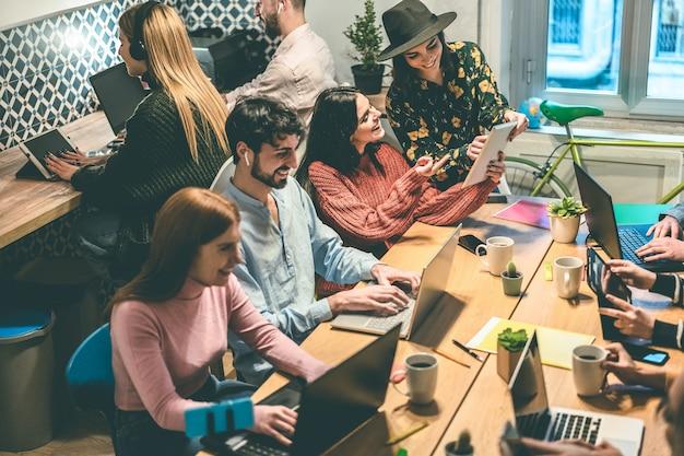 Młody zespół biznesowy pracujący w biurze coworkingowym - nieostrość na twarzy kobiety w centrum