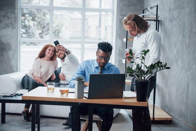 Młody zespół biznesu pracuje nad projektem z laptopem na stole i uśmiecha się
