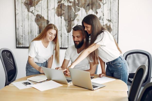 Młody zespół pracuje razem i korzysta z laptopa