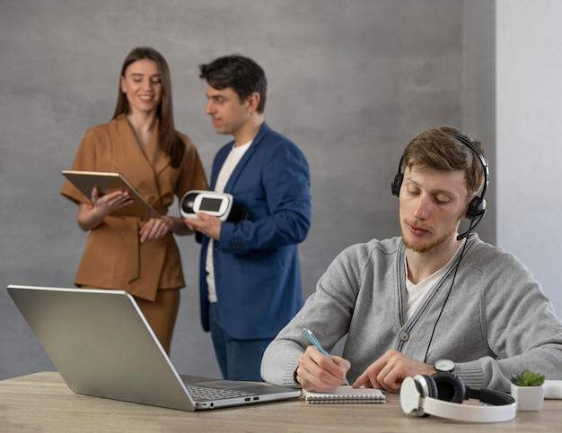 Młody zespół profesjonalnych ludzi korzystających z laptopa i zestawu słuchawkowego wirtualnej rzeczywistości