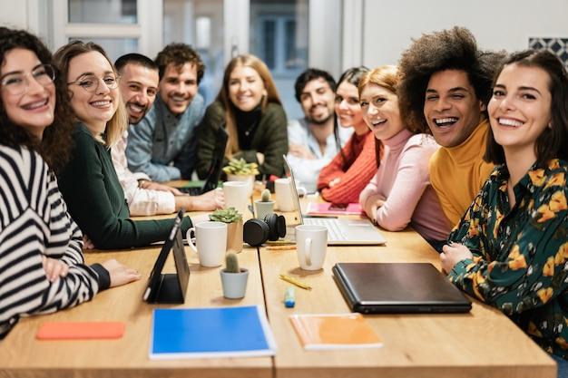 Młody zespół współpracowników bawi się dobrze pracując w nowoczesnym biurze startupowym - skoncentruj się na twarzy afrykańskiego mężczyzny
