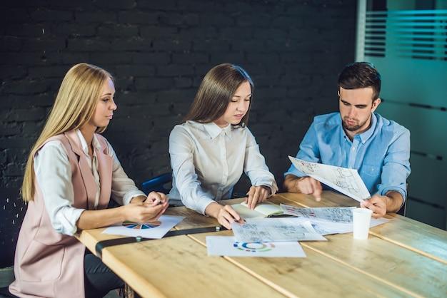 Młody zespół współpracowników oglądający storyboard do kręcenia wideo w nowoczesnym biurze coworkingowym